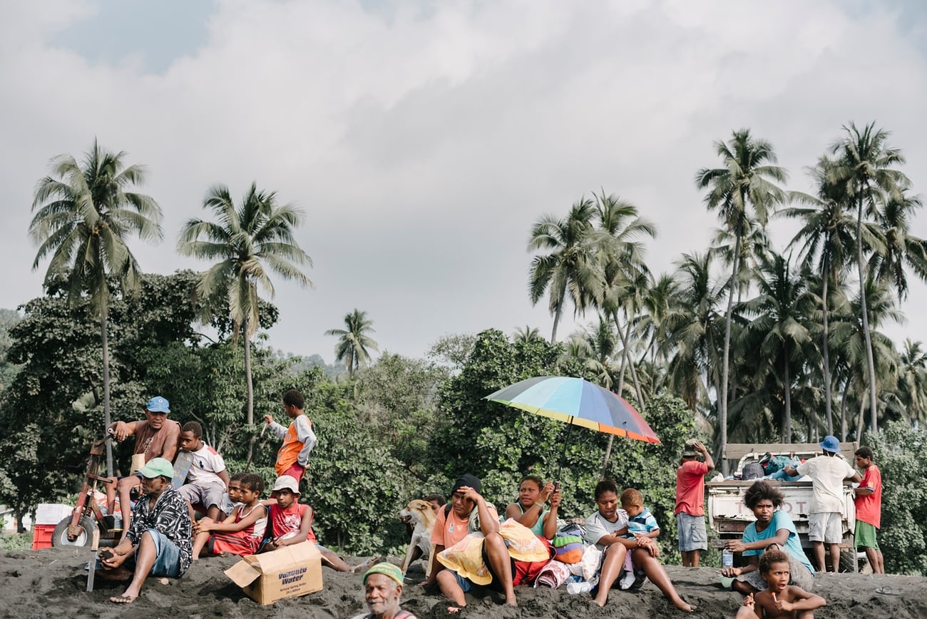 Residents from nearby villages gather with their belongings on beach near Lone, West Ambae awaiting evacuation to Santo. Photograph: Alana Holmberg for the Guardian