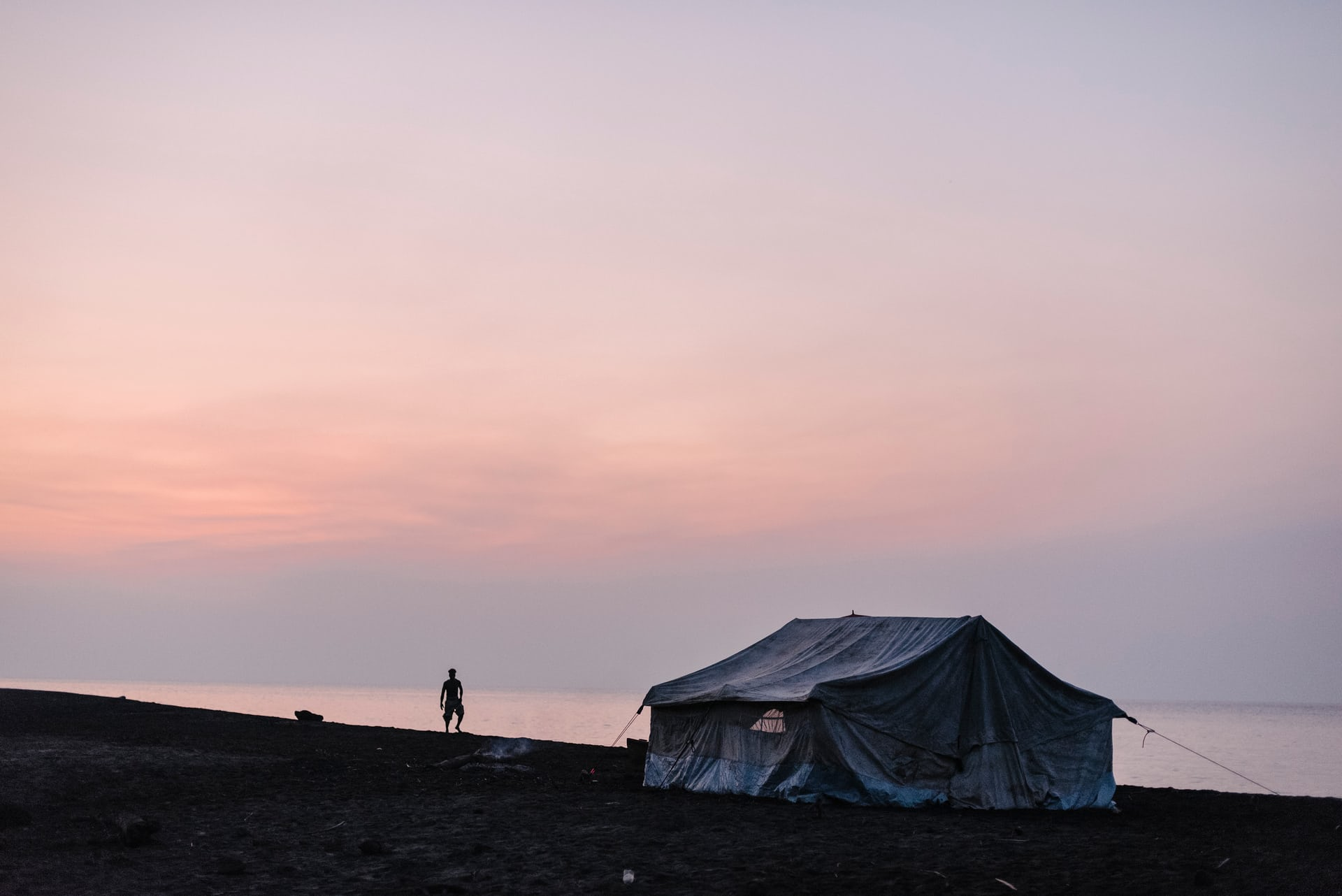 A man watches the sun set over Ambae Island. Communities from villages in the mountain were provided with tents for temporary housing when they evacuated to safer ground along the coastline in April due to volcanic activity. Photograph: Alana Holmberg for the Guardian