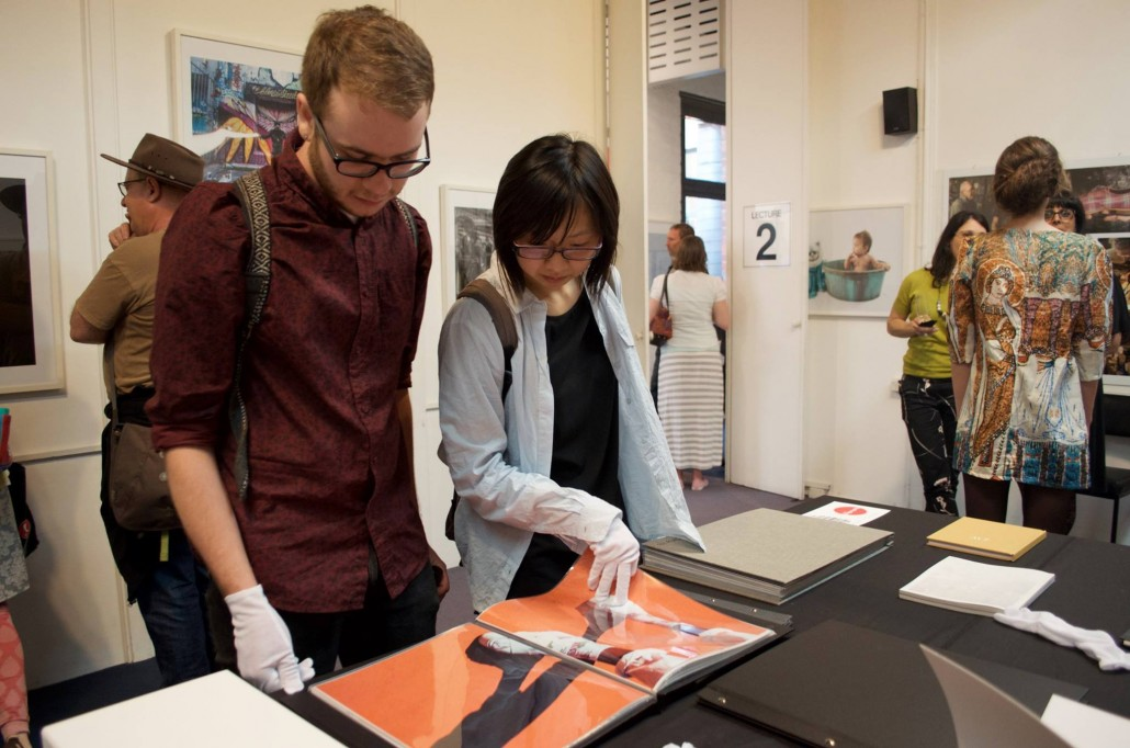 Students and guests looking at photobooks at PSC's End of the Year Exhibition