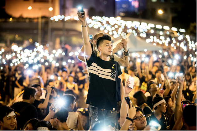 Mathew Lynn: 01 October 2014, Admiralty, Hong Kong.  'Occupy Hong Kong With Peace And Love' / 'Umbrella Revolution' protestors wave mobile phone LED's while singing in unity beside government buildings in Hong Kong. Protests began after the Standing Committee of the National People's Congress (NPCSC) came to a decision regarding proposed reforms to the Hong Kong electoral system.'