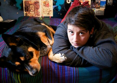 Samantha Shannon and her dog, Roxy lay down on her bed.